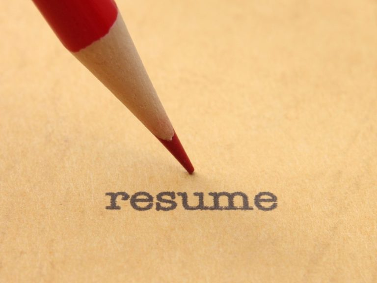 Red Pencil pointing at the word resume in typewriter type