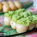 Foto van een drietal edamame dango, ofwel Japanse rijstcakejes op een stokje met edamame pasta.