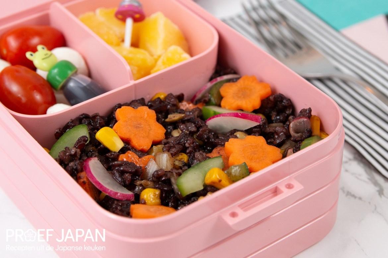 Foto van zwarte rijstsalade met yuzu dressing in een leuke roze bento box.