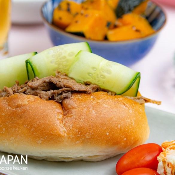 Proef Japan foto van ons recept voor teriyaki pulled chicken, geserveerd in een broodje met komkommer.