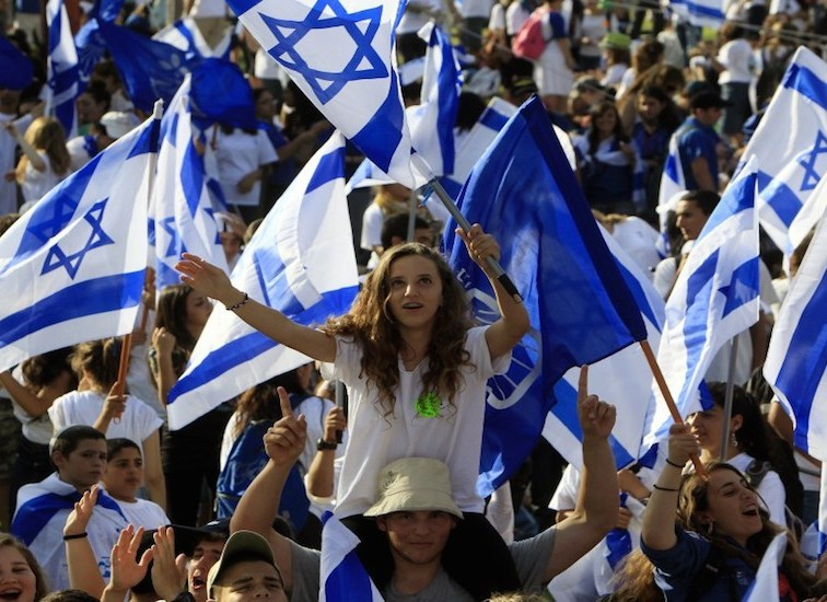 israeli-youths-wave-national-flags-940x550