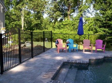 This is an 8 foot wide, continuous dome arched top gate in the Onguard Starling style. If you look closely, you'll see that the fence behind the chairs is black vinyl clad chain link. Pool code code chain link has a 1-1/4 inch diamond and makes it a bit easier on the eye than the standard 2x9. Using 1-1/4 inch chain link on a portion of the enclosure is a good way to contain costs and still create a nice, safe barrier.