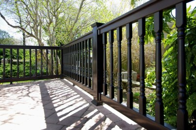 This black Grand Illusions 'T' top vinyl deck railing features Colonial balusters for an added touch of elegance.