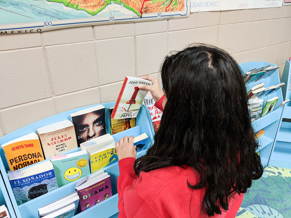 students selecting a book in class