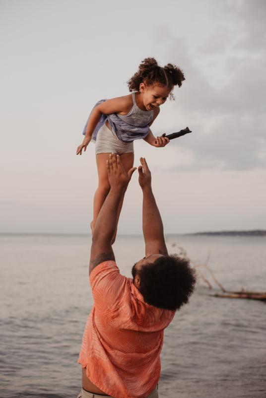 Padre jugando con hija en la playa