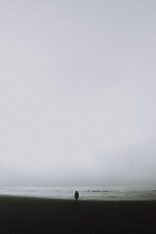 hombre caminando en la playa sin luz