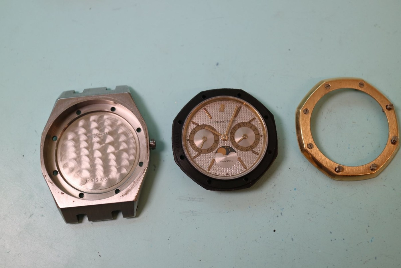 Back case, dial and movement, and bezel are separated prior to refinishing and service