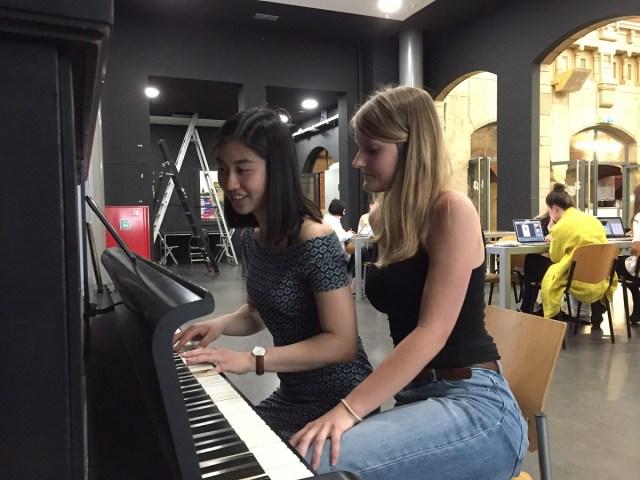 Twee studenten achter een piano