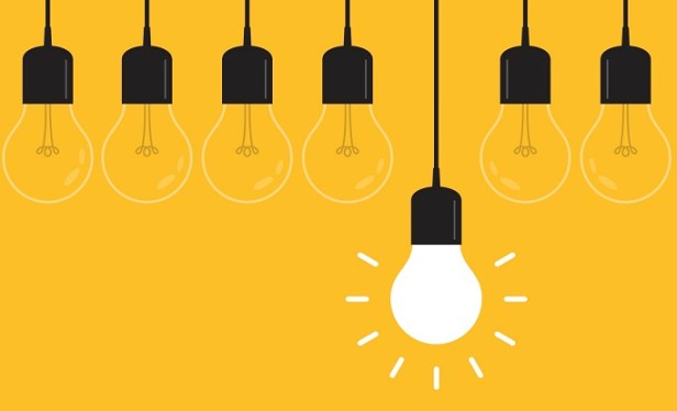 Hanging light bulbs with glowing one on yellow background