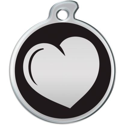 Eine runde Hundemarke mit einem metallischen Herzen auf einem schwarzen Hintergrund.