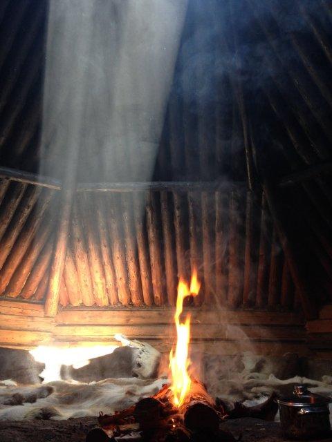 cabaña sami con sol y hoguera en Laponia sueca