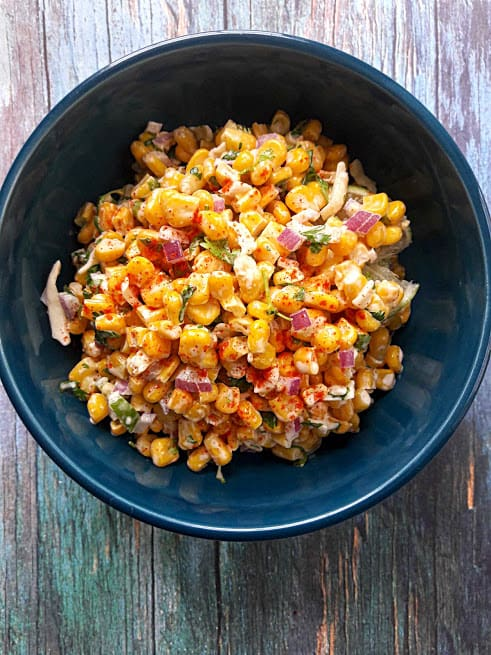 Sweet Corn Salad with spices, mayo, cheese and red onion served in blue bowl
