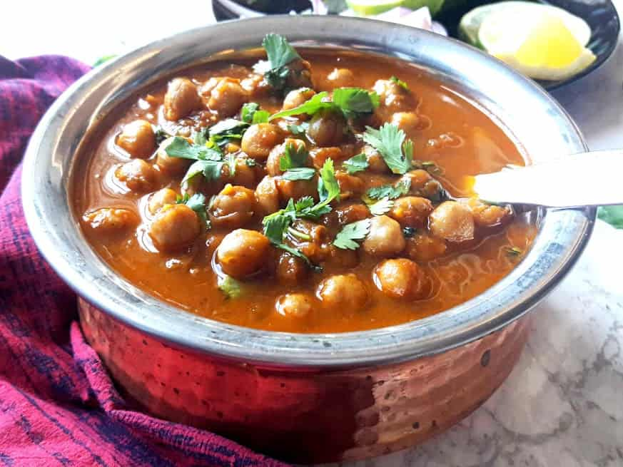 Punjabi Chole served in copper container with serving sppon inside