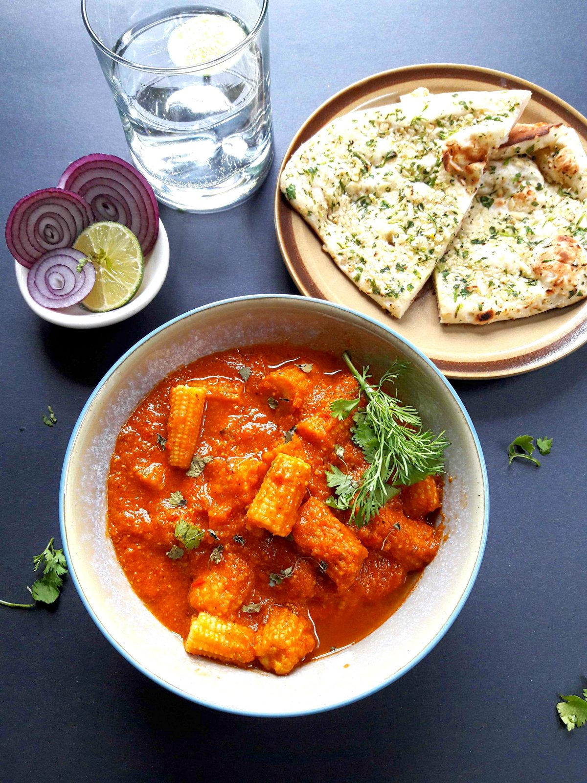 Dinner served with bowl of baby corn curry, naan and side of red onions and lemon salad along with glass of water on the side.