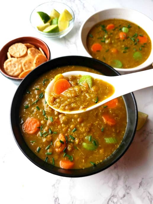 Lentil Quinoa Vegetables Soup with the soup spoon and gluten free crackers for the side.