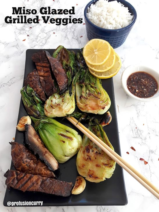 Miso Glazed Grilled Veggies served on black platter with rice and lemon wedges