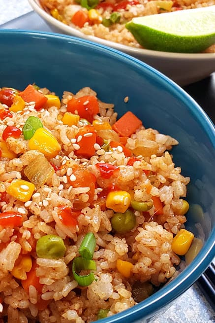 Close up image showing textures and layers of garnishes of Hibachi Vegetable Fried Rice