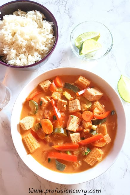 Chunks of assorted vegetables and tofu dunked in Thai red curry served with cooked Jasmine rice on the side and lime wedges. This classic curry is profusioncurry recipe.
