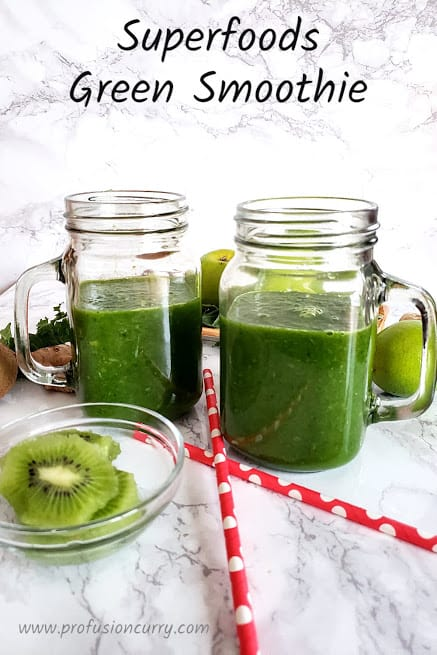 Two mason glass jars filled with Raw Green Smoothie. Two pink straws on the side for sipping it. A couple slices of kiwi for the munchin.