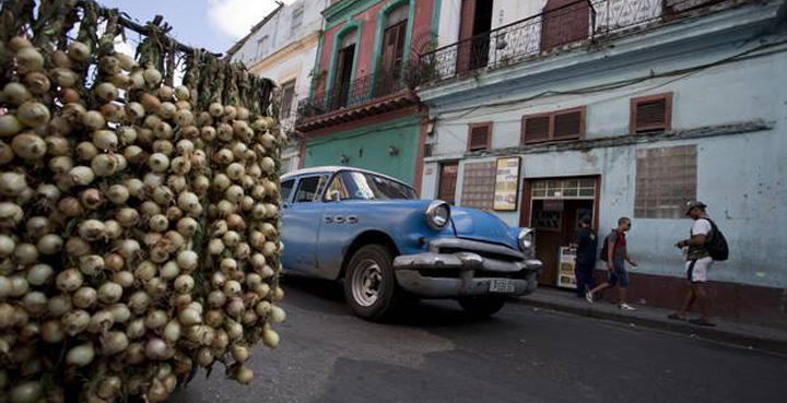 Un auto clásico norteamericano pasa junto a un vendedor de cebollas en La Habana. Desmond Boylan/ The Associated Press.
