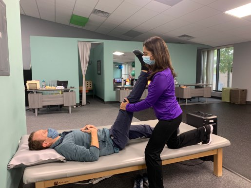 A PTA assists a patient with a supine hip flexor stretch.