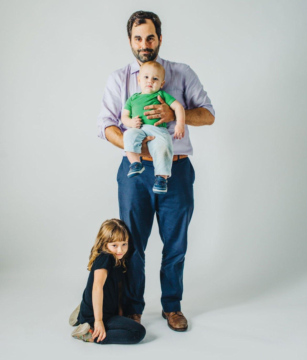 Frank de pie contra un fondo blanco con sus dos hijos, Jonah y Madeline