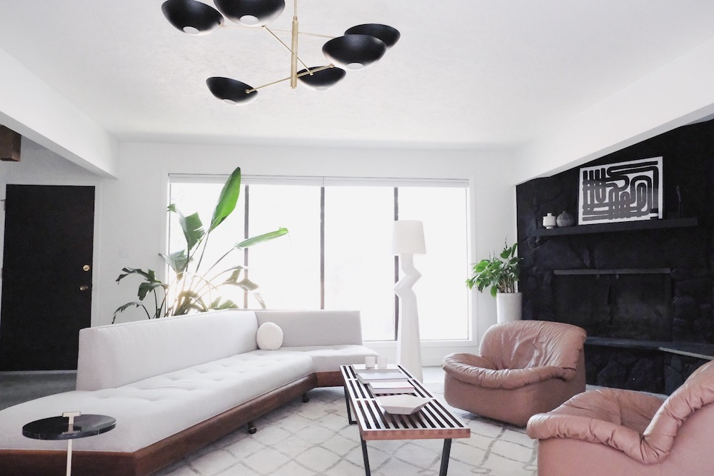 Family room at Kirsten Grove's residence featuring white sofa with pick chairs and black accent wall.