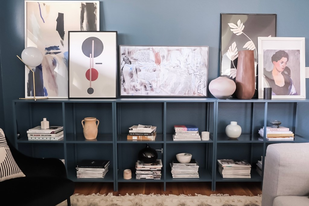 Living room decor and prop shelf with artwork stacked on top.