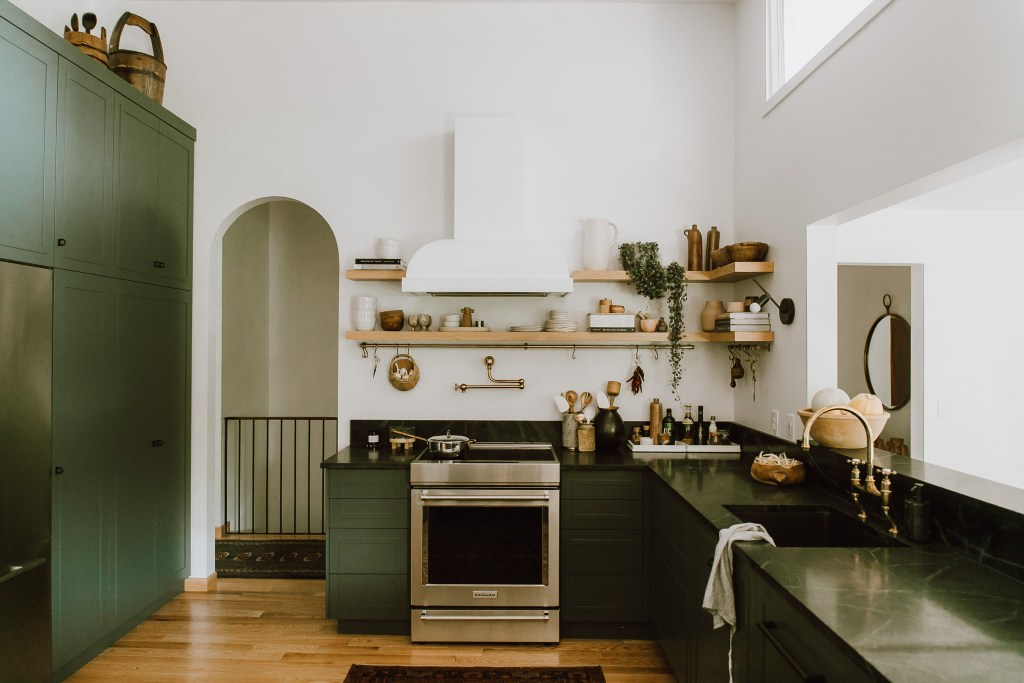 Smaller kitchen with U shape, wood floors and dark countertops and dark green cabinetry.