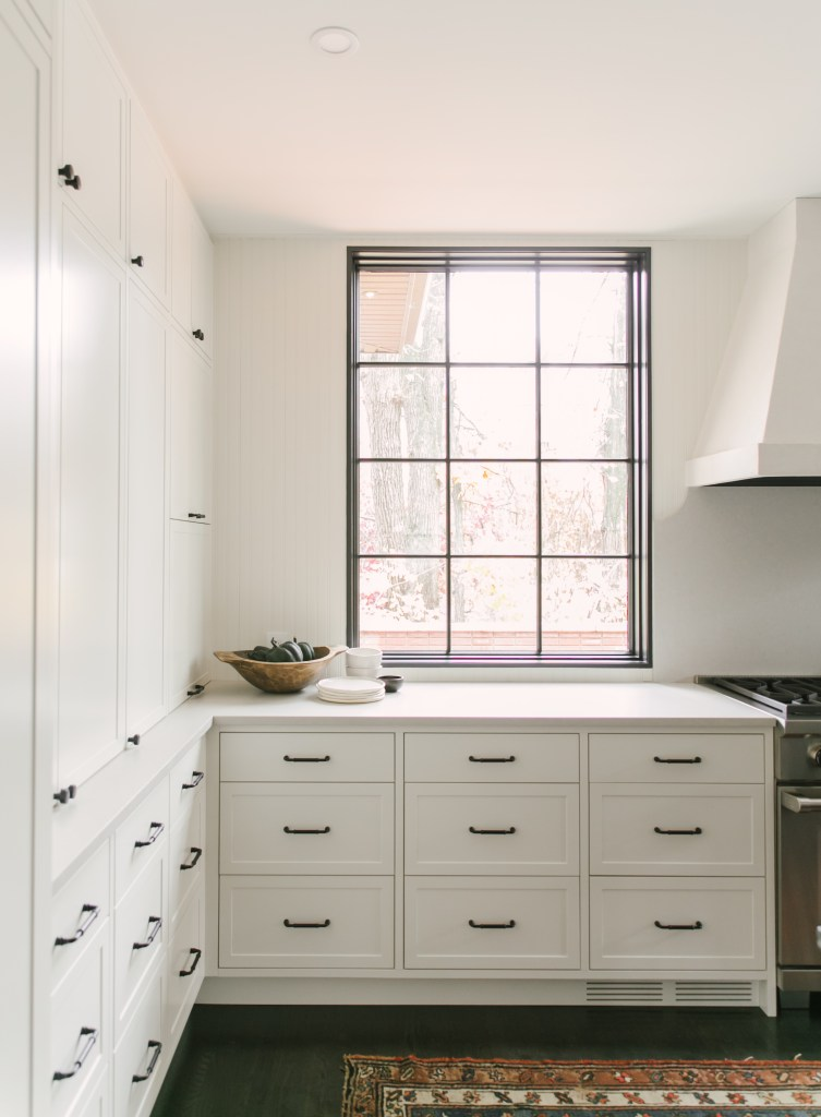 White cabinetry and white countertops to the left of the stove under a window.