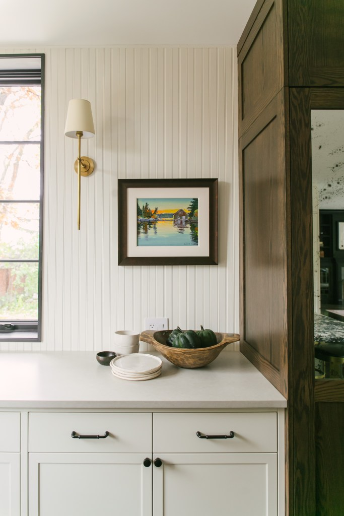 A closeup of the kitchen vignette by the wood cabinetry that transitions to the white cabinetry. Small accessories and artwork set the stage.