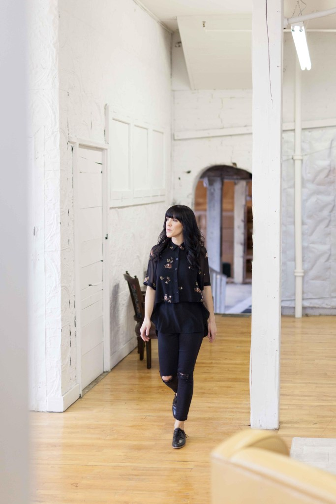 Portrait of Jaclyn Peters in interior design world exploring a warehouse.