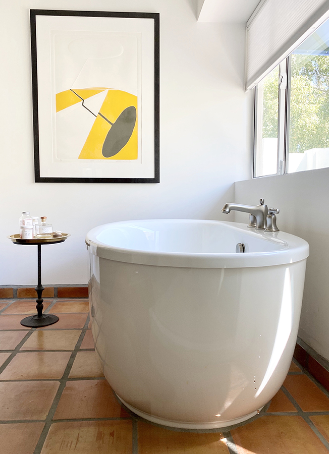 Natural light fills the master bathroom and shines through the window above the free-standing soaking tub.