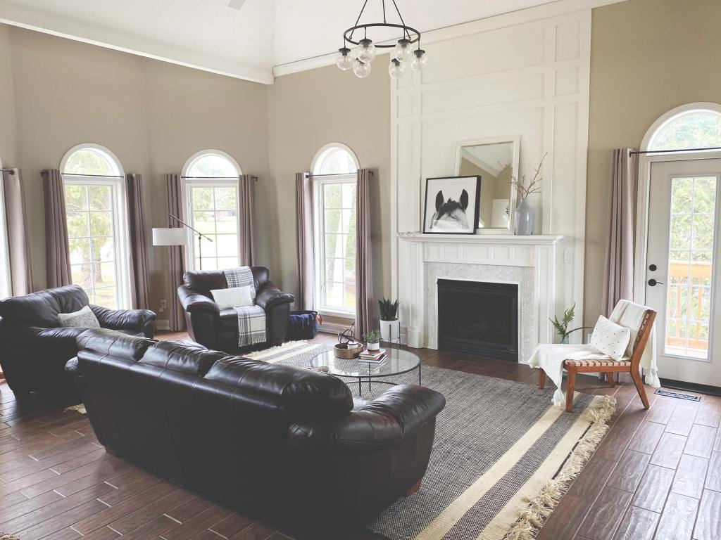 Completed look of the living room with area rug, leather furniture facing the fireplace.
