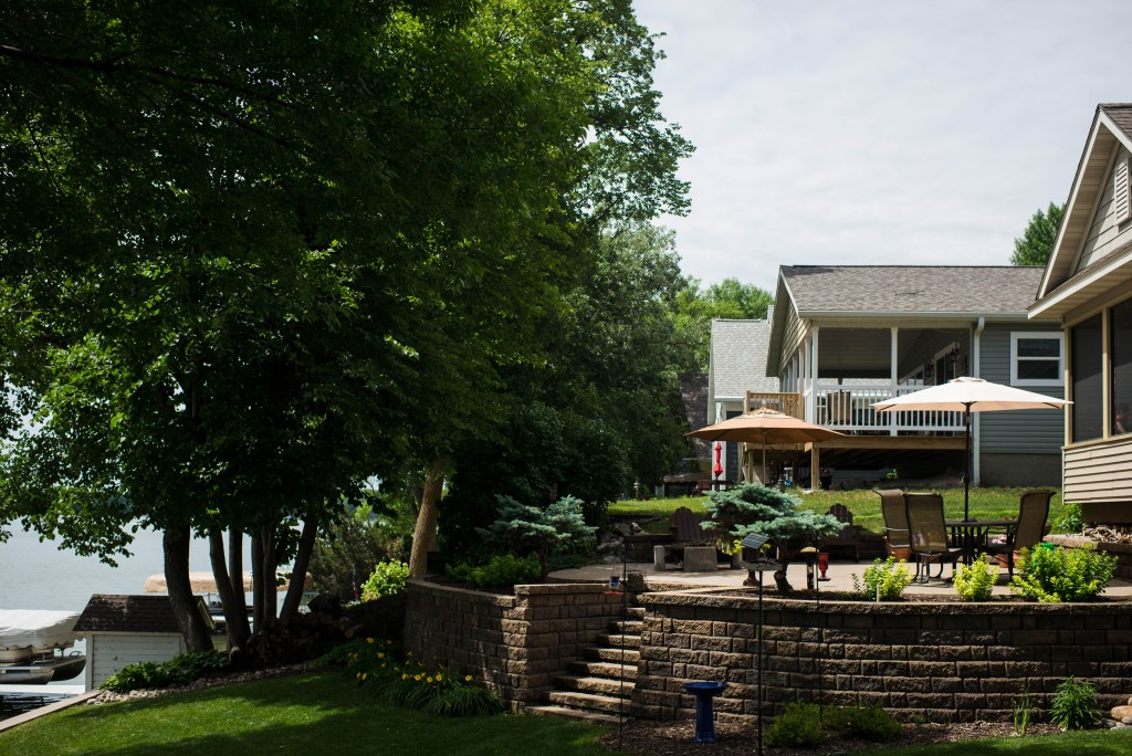 wide shot of the back yard showcasing a raised patio to the green grass and lake to the south