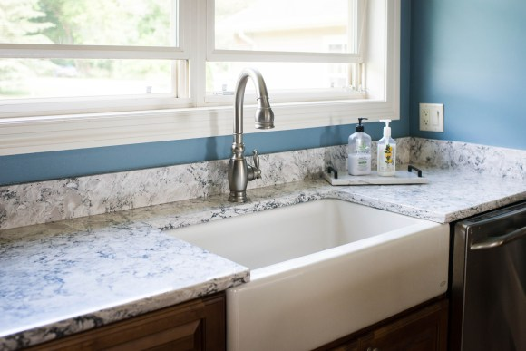 A  farmhouse sink paired with the existing faucet and white quartz countertops.