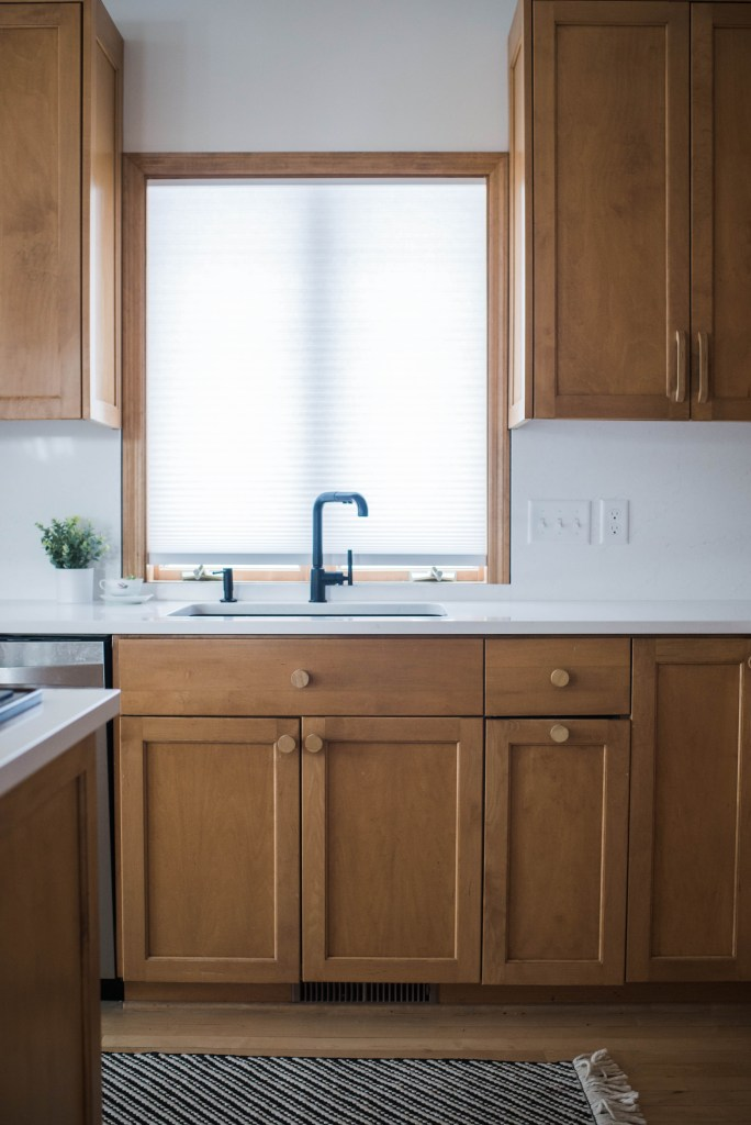 The kitchen has a minimal, organic and raw feel brought to life by the wood hardware.