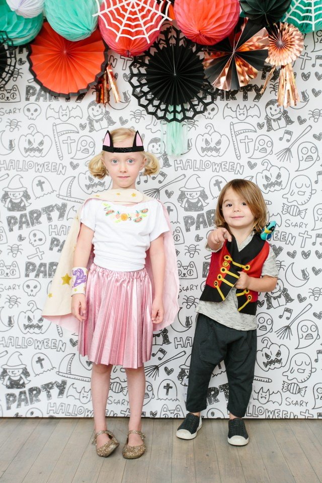 Halloween party photo backdrop and kids in costumes