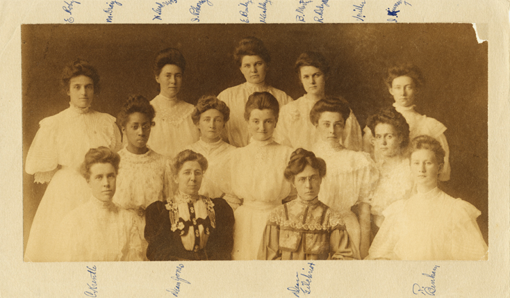 The graduating women of the class of 1907 sit for a senior portrait. Myrtle Craig sits in the far left of the second row. Image shows twelve female students and two female administrators.