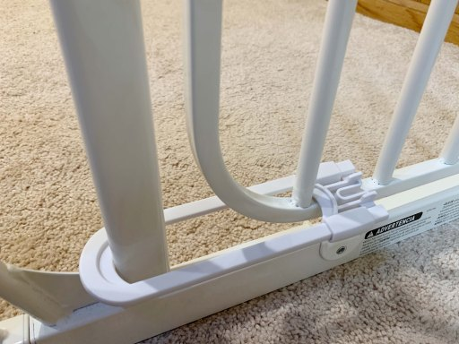 White baby gate with a white sliding cabinet lock on the floor