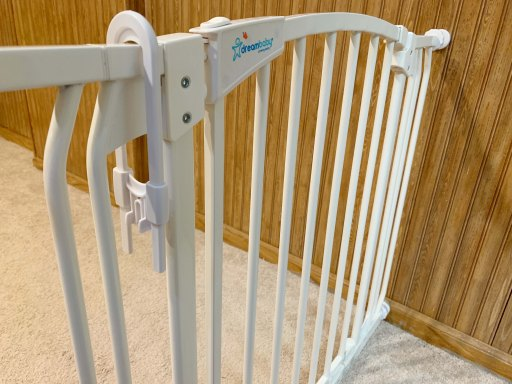 White baby gate with a white sliding cabinet lock
