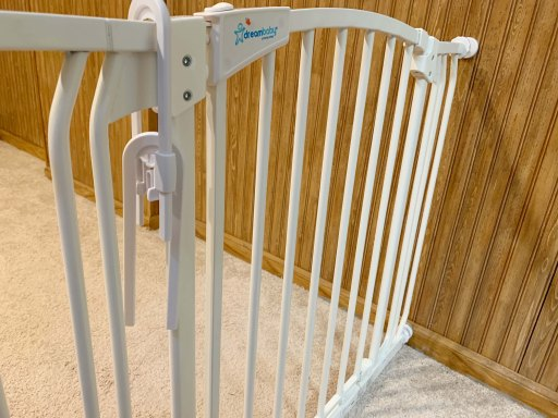 White baby gate with two white sliding cabinet locks