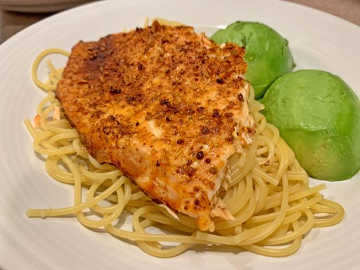 Piece of cooked salmon filet on a bed of spaghetti with two avocado halves on a white plate