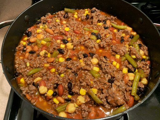 Colorful beans and veggies added to ground beef and crushed tomatoes in a black chili pot