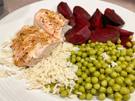 Chicken breast cut in half on a bed of white rice with green peas and red beets on a white plate