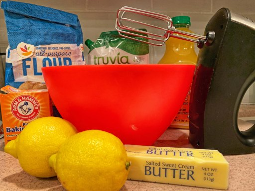 Butter, lemons, baking soda, flour, Truvia, Orange juice, a red mixing bowl, and an electric stirrer on a kitchen counter