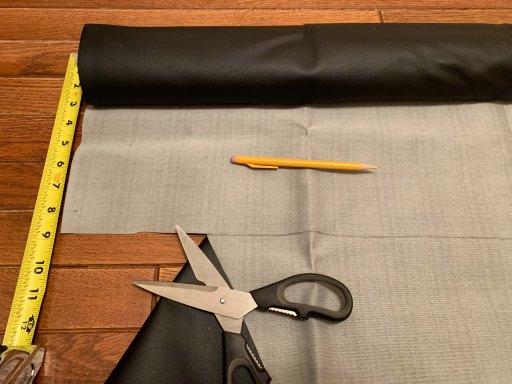 Black vinyl fabric, scissors, pencil, and tape measure on a hardwood floor
