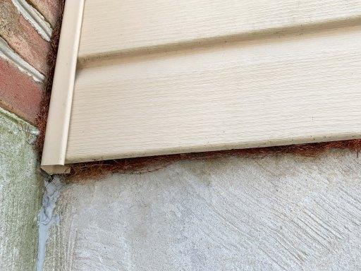 Copper mesh filling gaps in vinyl siding on a house