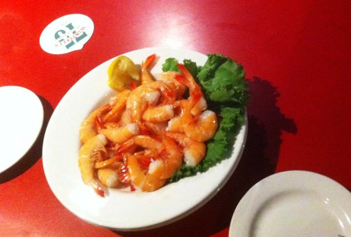 Shrimp on a white plate on a red dining table