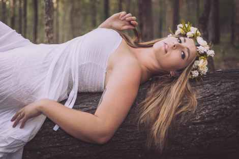 Women in white dress with crown of flowers lying down on a log